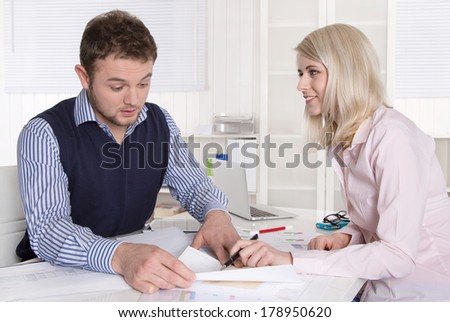 Two businesspeople working together at desk at office.