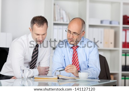 Two businesspeople working while having coffee at the office with binder - stock photo
