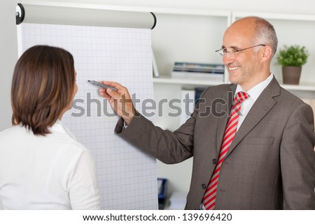 two businesspeople working with flipchart in the office - stock photo