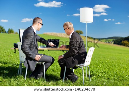 Two businesspeople working with laptop in a green meadow - stock photo