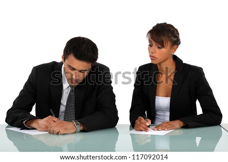 Two businesspeople writing at a desk - stock photo