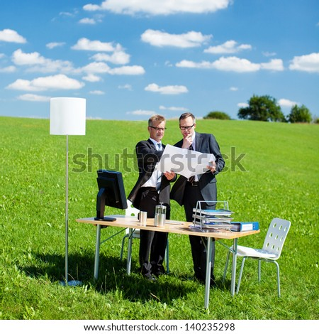 Two businesspersons planning something in a green meadow - stock photo