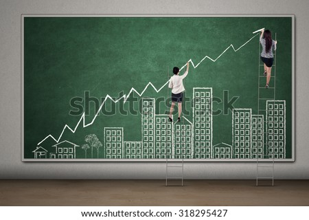 Two businesswoman draw increasing business property graph on the chalkboard with building and growing arrow