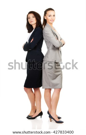 Two businesswoman leaning on each other. - stock photo