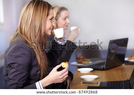 Two businesswoman sitting at conference table have a break during meeting - stock photo