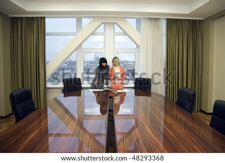 Two businesswoman working in a boardroom - stock photo