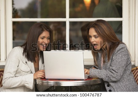 Two businesswomen at a cafe looking at a laptop