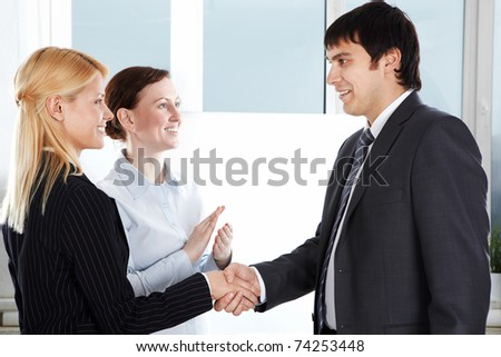 Two businesswomen congratulating a businessman and shaking hands with him
