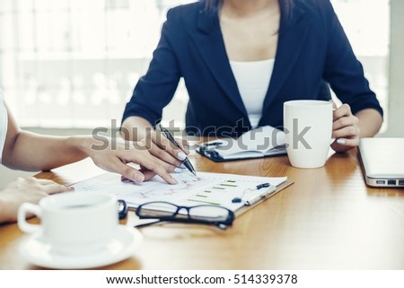 two businesswomen discussing on analysis chart
