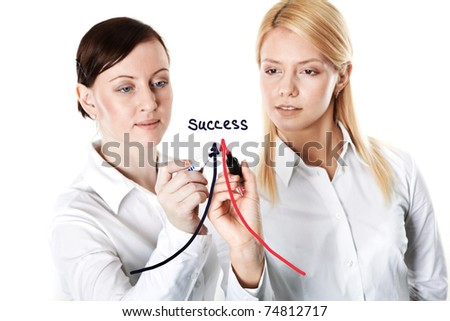 Two businesswomen drawing arrows leading to success - stock photo