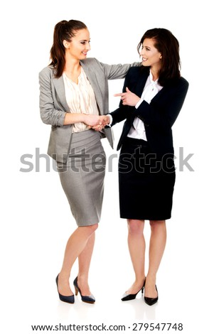Two businesswomen embracing and holding their hands. - stock photo