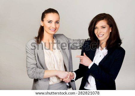 Two businesswomen embracing and holding their hands.