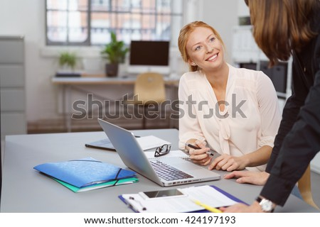 Two businesswomen enjoying a friendly chat at the office with a manageress or supervisor leaning over a table talking to a smiling happy employee