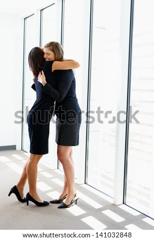 Two Businesswomen Hugging In Office - stock photo