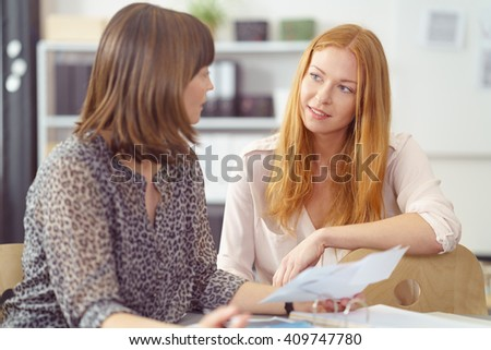 Two businesswomen in a serious discussion seated at a desk together looking at paperwork, focus to an attractive young redhead