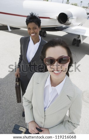Two businesswomen in front of private plane - stock photo
