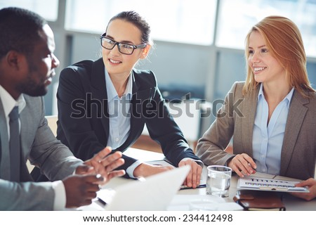 Two businesswomen interviewing young man - stock photo