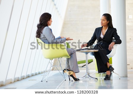 Two Businesswomen Meeting Around Table In Modern Office - stock photo