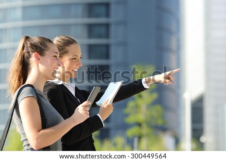 Two businesswomen searching location with mobile phone gps and paper map with office buildings in the background - stock photo