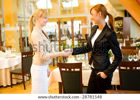 Two  businesswomen shake hands and conclude a deal. They're in restaurant.
