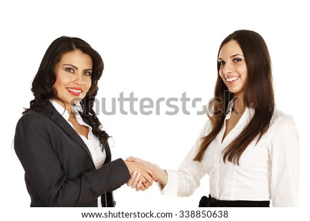 Two businesswomen shaking hands. Both women smiling and looking at camera.
