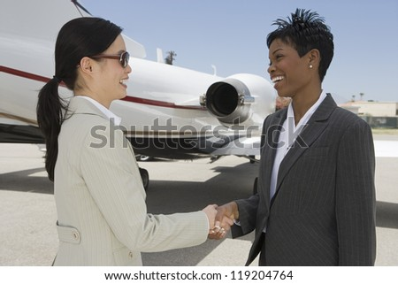 Two businesswomen shaking hands in front of private plane - stock photo
