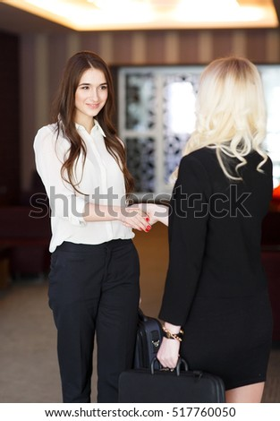 Two Businesswomen Shaking Hands In Modern Office