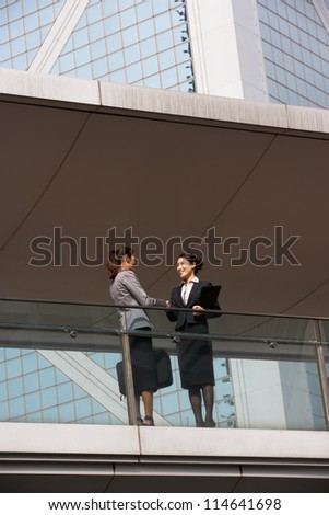 Two Businesswomen Shaking Hands Outside Office Building - stock photo