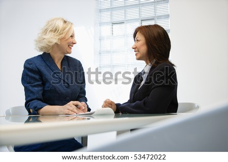 Two businesswomen sitting at office desk looking at eachother smiling. - stock photo