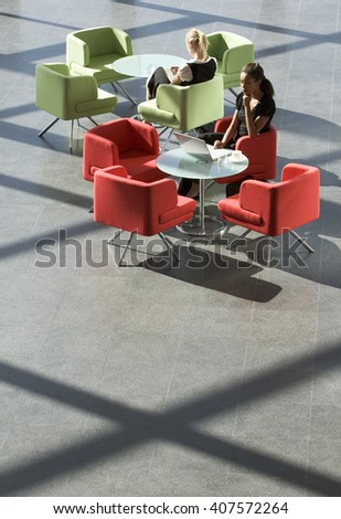Two businesswomen sitting at tables in an office building - stock photo