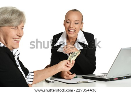 Two businesswomen sitting at the table on a white background - stock photo