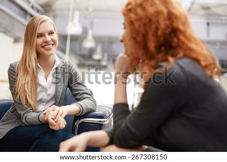 Two businesswomen speaking at meeting or during break - stock photo