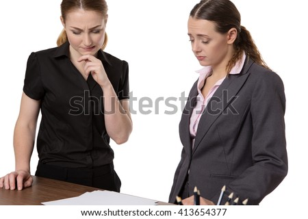 Two businesswomen standing at an office desk having meeting and discussing paperwork.