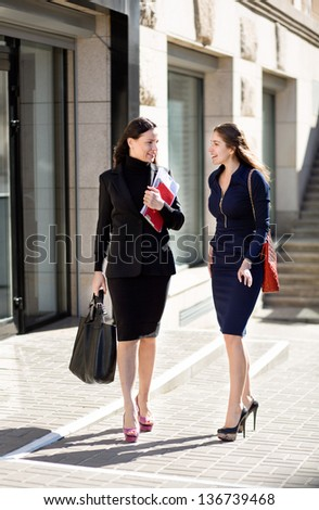 two businesswomen standing on the building background and look at each other - stock photo