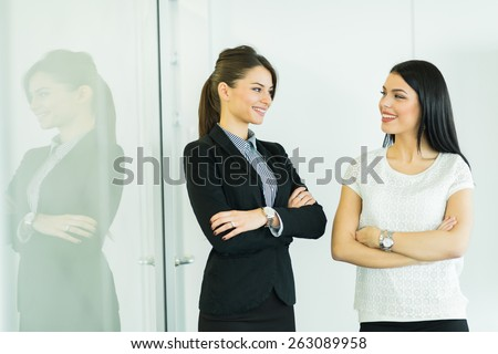 Two businesswomen talking in an office with reflection on the glass behind them - stock photo