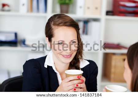 Two businesswomen talking while drinking coffee inside the office - stock photo
