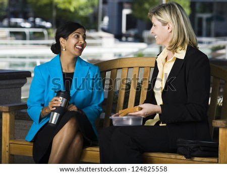 Two businesswomen talking while sitting on bench outdoors