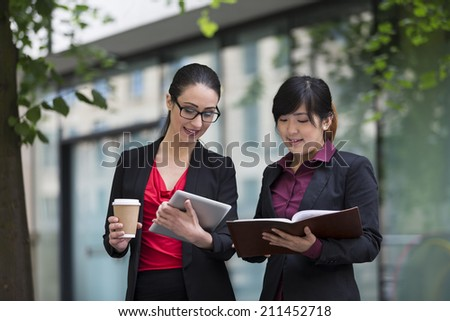 Two businesswomen with digital tablet in a modern urban setting. Caucasian and Asian business women. - stock photo