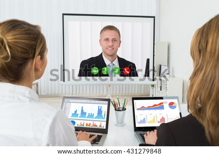 Two Businesswomen With Graphs On Laptop Videoconferencing In Office - stock photo