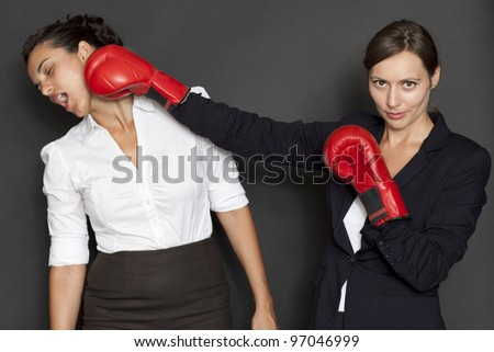 Two businesswomen with red boxing gloves