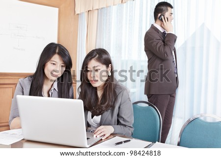 Two businesswomen working on the laptop while businessman phone on background - stock photo