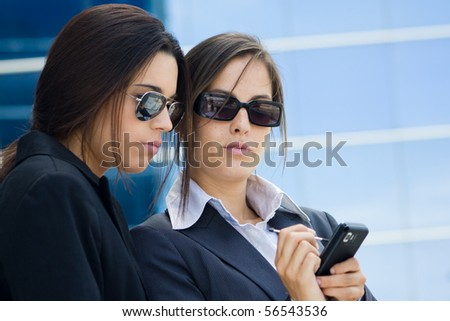 two businesswomen working referring to a mobile phone - stock photo