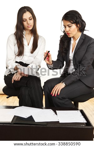 Two businesswomen working together discussing and looking at papers.