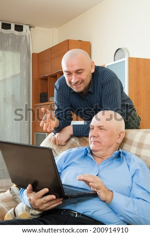 two bussinesmen using laptop at home interior - stock photo