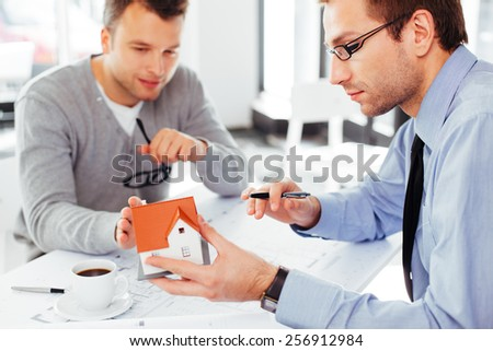 Two busy architects discussing their design - stock photo
