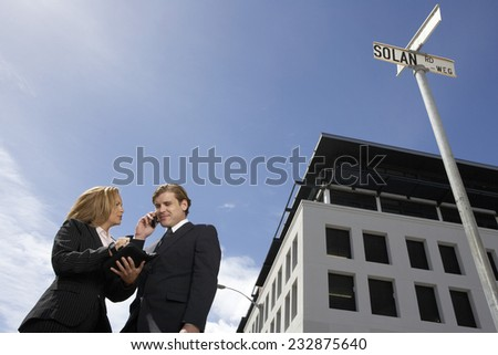Two Busy Businesspeople on Street Corner - stock photo