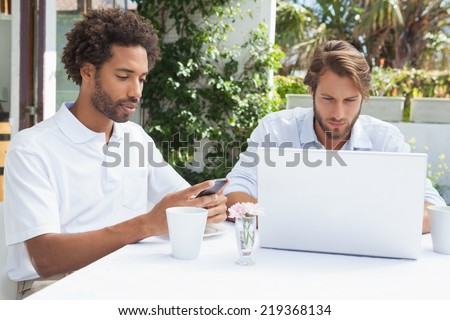 Two busy friends having coffee together outside at the coffee shop - stock photo