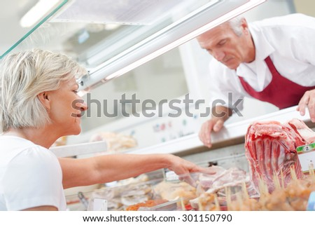Two butcher checking their display is neat - stock photo