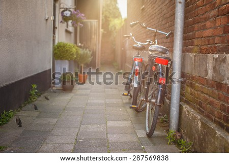 Two bycicles near stone wall on the old street. - stock photo