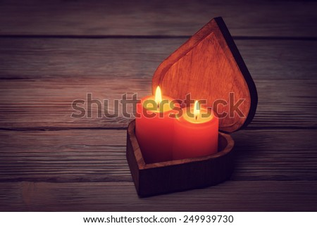 Two candles in open heart shaped box on vintage wooden background - stock photo